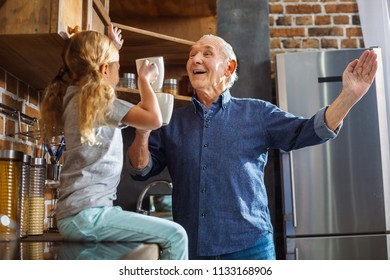 Warm time. Joyful smiling elderly man having fun with his granddaughter while drinking tea in th ekitchen