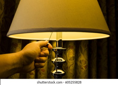 Warm tone imaged of hand turning of lamp in bedroom