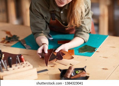 Warm toned close up of young  artisan holding leather pieces  in shoemaking  workshop, copy space
