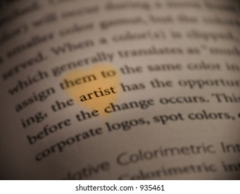 A warm toned heart encircles the word artist in a book