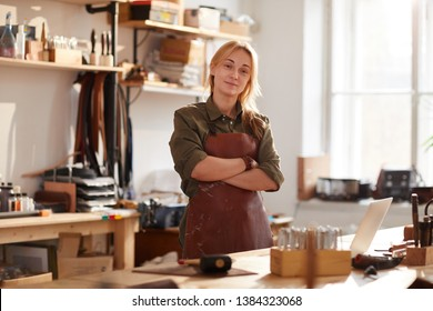 Warm toned portrait of confident female artisan standing with arms crossed while posing in workshop