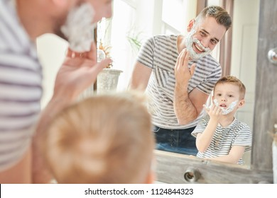 Warm toned portrait of handsome dad teaching cute little son how to shave, standing against mirror with faces covered in foam in modern bathroom