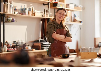 Warm toned portrait of smiling female artisan standing with arms crossed while posing in workshop