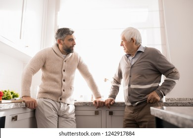 Warm toned waist up portrait of bearded adult man talking to his father in kitchen lit by sunlight
