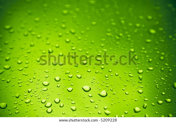 Warm toxic-green water drops over glass background