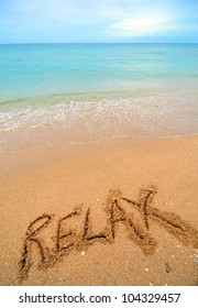 A warm tropical beach with blue water and waves and relax written in the sand