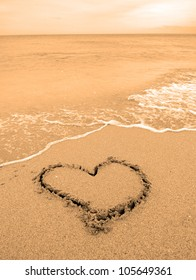 A warm tropical beach with waves and a heart drawn in the sand