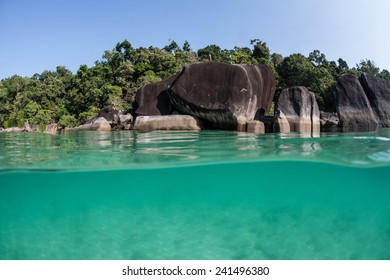 Warm, tropical water bathes the rocky shore of a remote island in the Mergui Archipelago off the coast of Myanmar. These beautiful islands in the Andaman Sea are rarely visited.