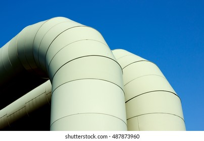 Warm water heating, close-up (detail) light green large pipes knee (elbow, knee-piece) from thermal power station to the cities, blue sky.