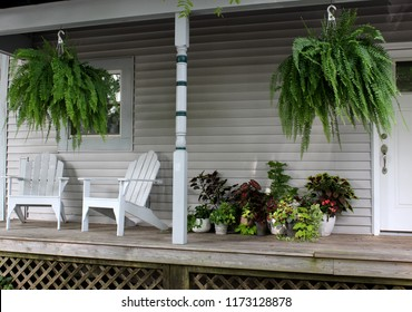 Warm and welcoming Southern front porch, with potted plants, hanging ferns and two Adirondack chairs for visiting.