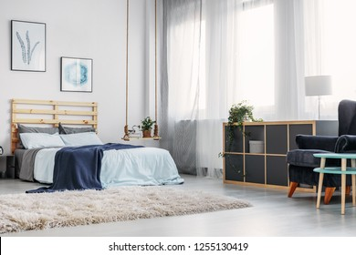 Warm white carpet on the floor of elegant bedroom with double bed with wooden headboard and blue blanket