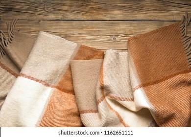Warm wool blanket thrown on wooden background