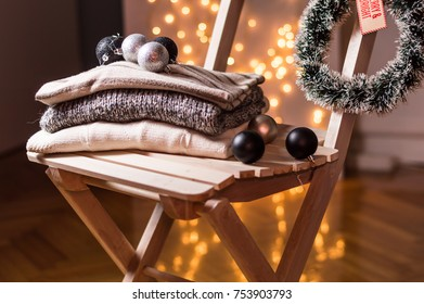 Warm wool sweaters and Christmas decoration on the chair. Christmas holiday celebration concept