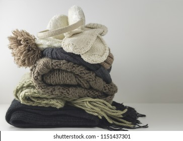 Warm woolen knitted winter and autumn clothes, folded in a pile on a white table. Sweaters, scarves, gloves, hat, headphones. Place for text. Copyspace