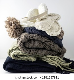 Warm woolen knitted winter and autumn clothes, folded in a pile on a white table. Sweaters, scarves, gloves, hat, headphones. Square format