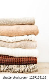 Warm woolen sweaters and pullovers stack on white background. Woman fashion clothes on white background.