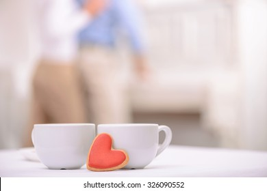 Warm your heart. Two cups of tea standing on the table with adult couple embracing on the background