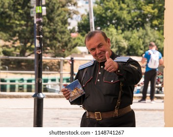 Warmemunde, Germany - June 8, 2018: Middle aged caucasian man German uniform smiling and giving thumbs up and holding a CD he is trying to sell