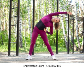 Warming up before workout. Fit caucasian young woman in magenta sportswear does side bends in sports area outdoor in summer, selective focus. Fitness, active morning, training and healthy lifestyle