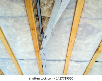 Warming of the ceiling with mineral basalt wool and reinforced polyethylene film. Thermal insulation of the house, energy efficiency for heating in winter. Selective focus.