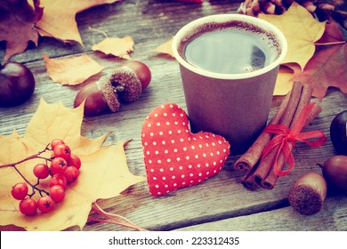 warming coffee cup, red heart and autumn still life on old table