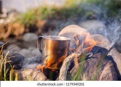 Warming cup of tea or coffee on burning campfire at wild camping