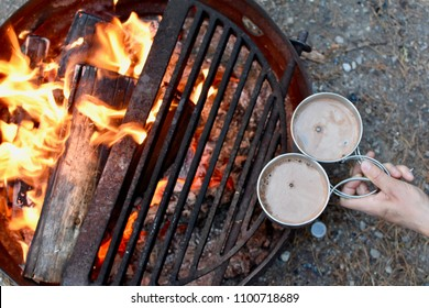 Warming mugs of hot chocolate over a camp fire