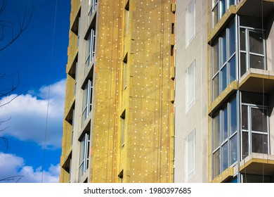 Warming of a multi-story residential building facade with a mineral wool, rock wool. External insulation of apartments, houses facades. Repair work on a construction object. Heat and sound insulation.