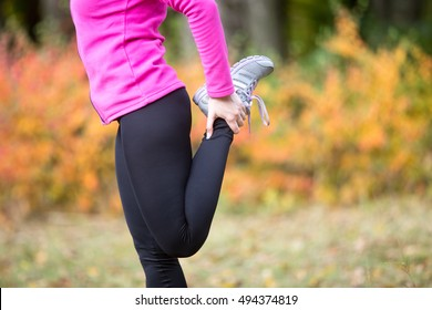 Warming up outdoors in the fall, stretching after or before running. Quadriceps standing. Closeup