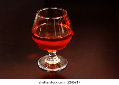 A warming snifter of Amaretto liquor on a table awash in a soft glowing light