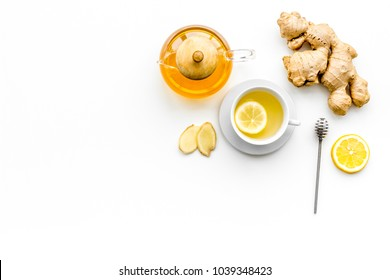 Warming tea with lemon and ginger. Cup, teapot, ginger root on white background top view copy space