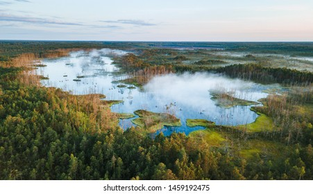 Warmly colored sunrise over a foggy swamp. Aerial view of stunning landscape at peat bog at Cenas Tirelis in Latvia. Wooden trail leading along the lake surrounded by pounds and forest.