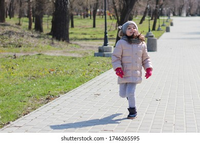 Warmly dressed little girl in mittens runs in the park