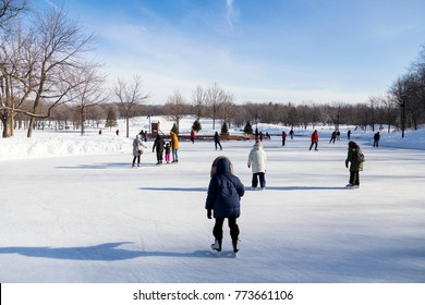 Warmly dressed people skating on frozen lake surrounded by pristine snowy landscape during beautiful sunny day, Beaver Lake, Mount Royal, Montreal, Quebec, Canada