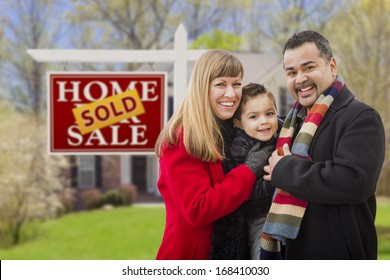 Warmly Dressed Young Mixed Race Family in Front of Sold Home For Sale Real Estate Sign and House.