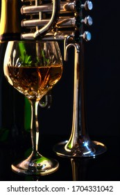 Warmly Lit Wine Glass with Piccolo Trumpet and Green Bottle in Background