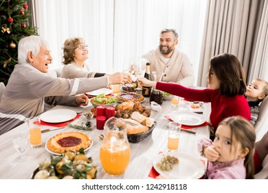 Warm-toned portrait of big happy family enjoying Christmas dinner together and clinking glasses