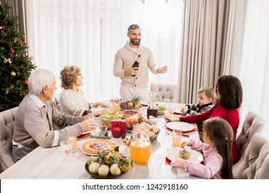 Warm-toned portrait of big happy family enjoying Christmas dinner together with mature father hosting table, copy space