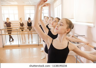 warm-up sessions at the bench, the girls doing ballet. young ballerinas dressed in black swimsuits warm up and stretch near ballet bar