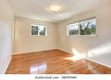Warn colors empty room with two small windows and hardwood floor
