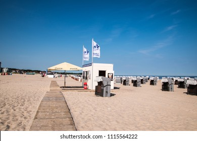 Warnemunde, Germany - June 8, 2018: Rows of beach chair huts and a snack bar located on the beautiful white sand beaches of the northern Germany coastal city of Warnemunde before the tourists arrive