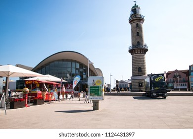 Warnemunde, Germany - June 8, 2018: Landmark lighthouse and shops in beach town of Warnemunde, Germany as seen on this date
