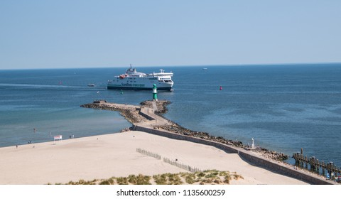 Warnemunde, Germany - June 8, 2018: A large ferry is seen entering the port of Warnemunde, Germany as it passes a small green lighthouse on this date