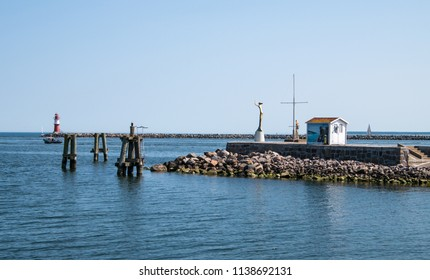 Warnemunde, Germany - June 8, 2018: Entrance to Warnemunde harbor including view of Esperanda golden statue and the small red and white lighthouse