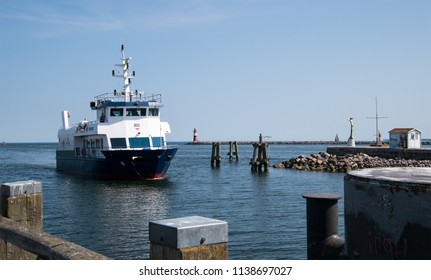 Warnemunde, Germany - June 8, 2018: A boat is seen entering Warnemunde harbor, as it passes a red lighthouse and the Esperanda golden statue.