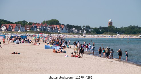 Warnemunde, Germany - June 8, 2018: View of the beach and Baltic Sea crowded with tourists in this coastal resort town on a beautiful warm sunny day.