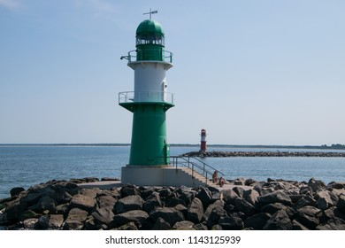 Warnemunde, Germany - June 8, 2018:  Small green and white lighthouse and red and white lighthouse at mouth of Warnemunde harbor on this date.