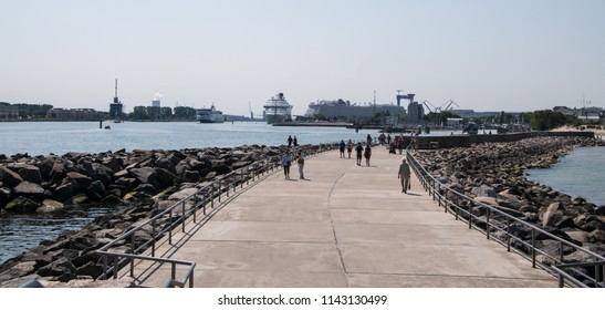 Warnemunde, Germany - June 8, 2018: Wide sidewalk with tourists in the port town of Warnemunde, Germany with large cruise ships in the distance