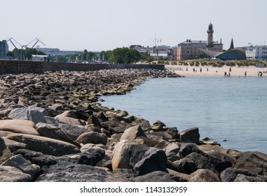 Warnemunde, Germany - June 8, 2018: Landmark lighthouse and shops in beach town of Warnemunde, Germany as seen from the rock jetty on this date