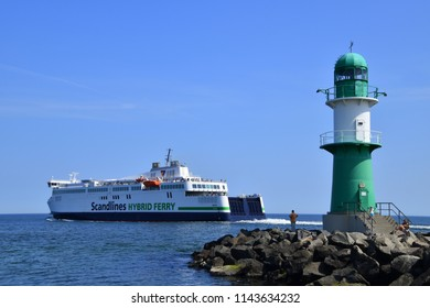 Warnemunde, Germany - June 8, 2018: A large ferry is seen leaving the port of Warnemunde, Germany as it passes a small green lighthouse on this date